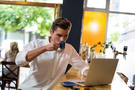 Man having coffee while using laptop in café