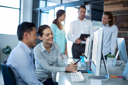 Businesspeople interacting while working on personal computer in office