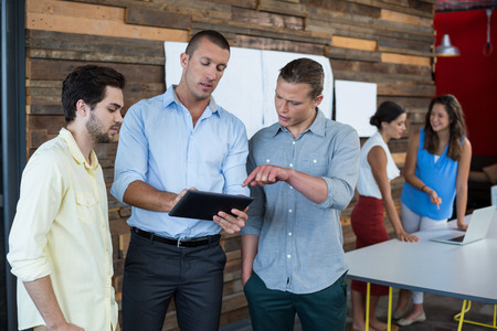 Business executives discussing over digital tablet in office
