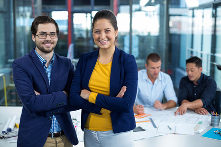 Male and female business executive smiling while colleague interacting over blueprint in background at office