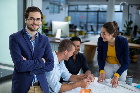 Male graphic designer smiling while colleague interacting over blueprint in background at office