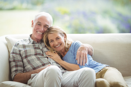 Portrait of smiling senior couple sitting together on sofa in living room at home