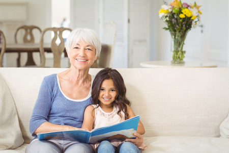 Portrait of smiling grandmother and granddaughter sitting together on sofa with photo album