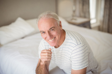 Portrait of happy senior man sitting on bed in bedroom at home