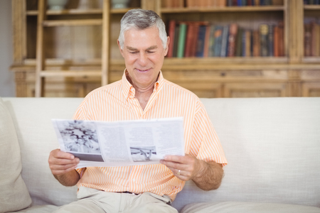 Senior man reading newspaper in living room at home