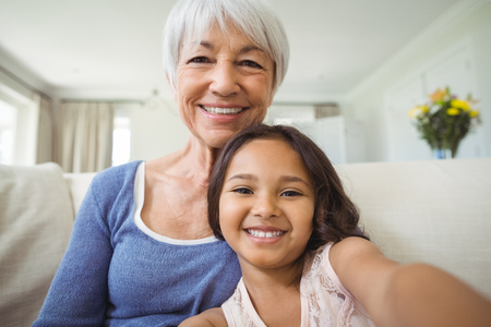 Portrait of smiling granddaughter and grandmother sitting on sofa in living room at home