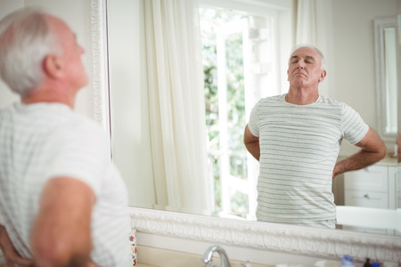 Senior man stretching in front of the mirror in bathroom