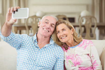 Senior couple taking a selfie on mobile phone in living room at home
