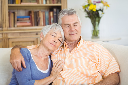 Senior couple relaxing on sofa in living room at home
