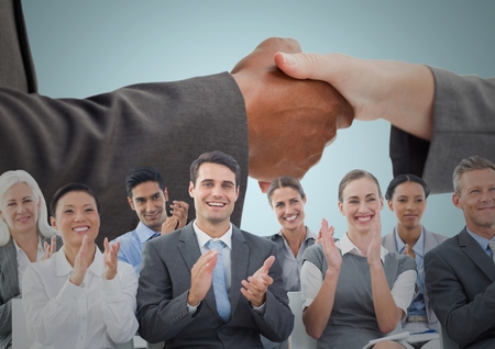 Digital composite of Handshake with business people and blue background