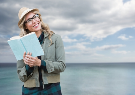 Digital composite of Woman with book in front of seaの写真素材