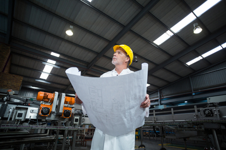 Thoughtful factory engineer holding blueprint in bottle factory
