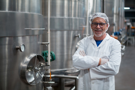 Portrait of smiling factory engineer standing with arms crossed in bottle factory