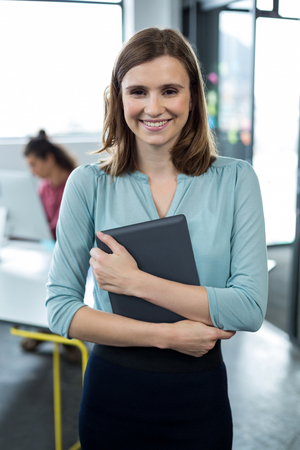 Portrait of business executive standing with digital tablet in office