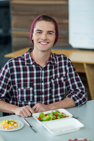 Portrait of smiling business executive having meal in office