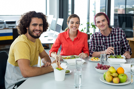 Portrait of smiling business executives having meal in office