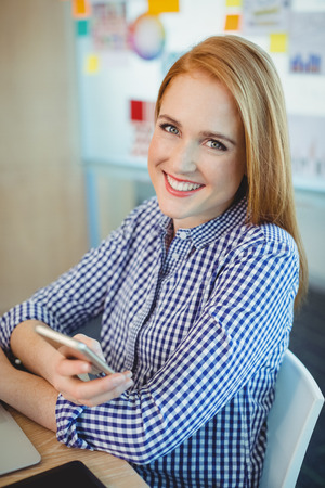 Portrait of female graphic designer holding mobile phone in office