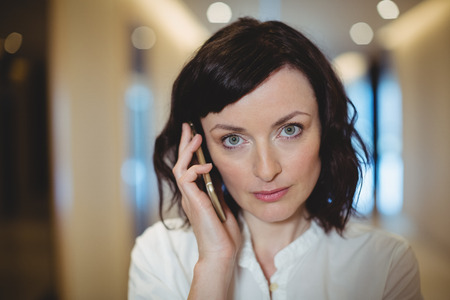 Portrait of female business executive talking on mobile phone in corridor of office
