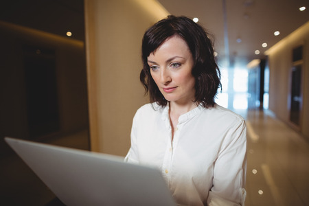 Female business executive using laptop in corridor of office