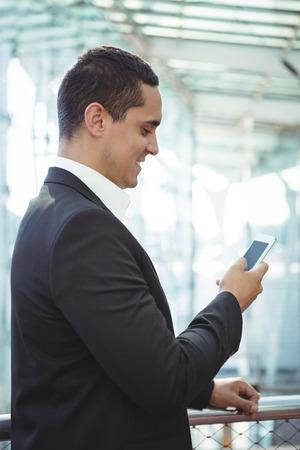 Smiling businessman using mobile phone on platform