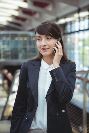 Smiling businesswoman talking on mobile phone on platform