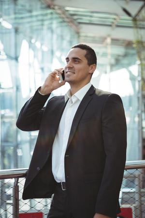 Smiling businessman talking on mobile phone on platform