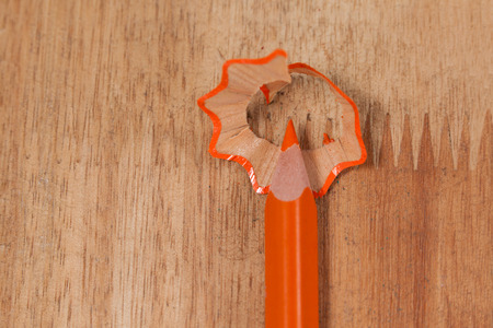 Close-up of orange colored pencil with shavings on wooden background