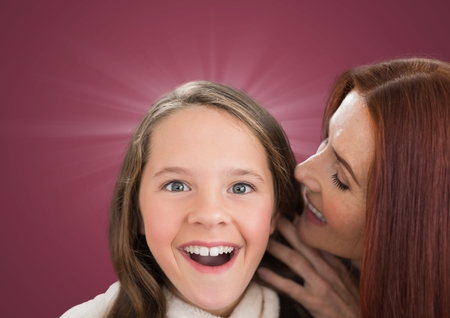 Digital composite of Mother speaking to her dautgher ear against a dark pink backgroundの写真素材