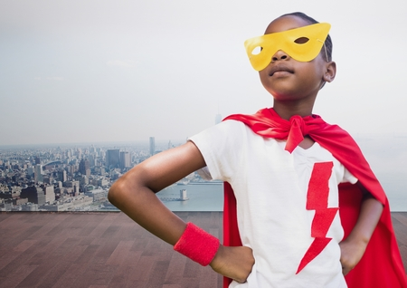 Composite image of kid wearing red cape and yellow mask standing with hand on hip against cityscape background