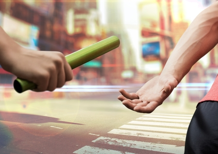 Digital composite image of hands passing the baton against cityscape background
