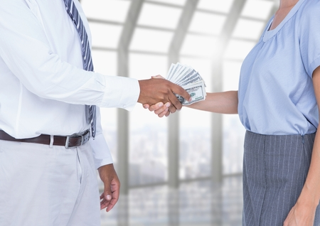 Businessman bribing partner while shaking hands in office