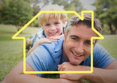 Digital composition of dad and son laying in the park against house outline in background