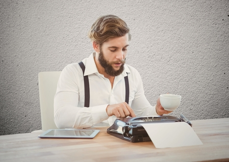Businessman typing on typewriter with digital tablet at desk
