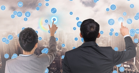 Digital composition of business executives touching technology icons against cityscape