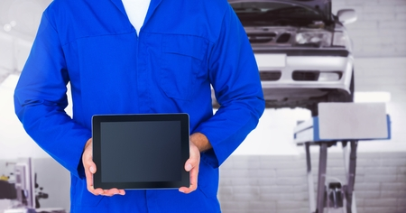Mid section of mechanic holding a digital tablet at workshop