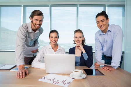 Portrait of smiling business executives in conference room at office