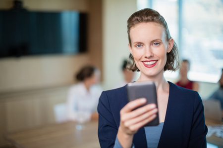 Portrait of beautiful business executive talking on her mobile phone in conference room