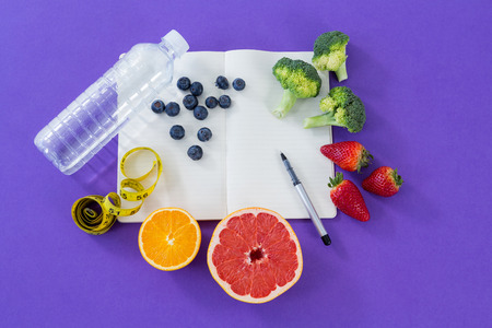 Water bottle, measuring tape, various fruits, vegetable, opened book and pen on purple background