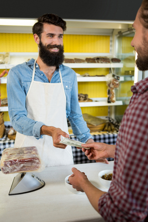 Customer paying bill by cash at meat counter in market