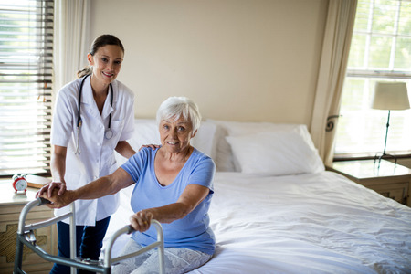 Female doctor helping senior woman to walk with a walker at home