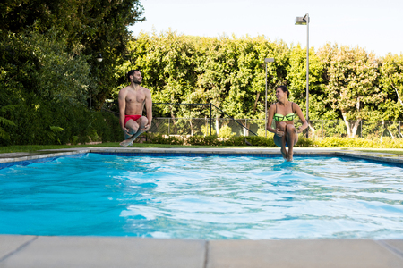 Young couple jumping together in the pool on a sunny day