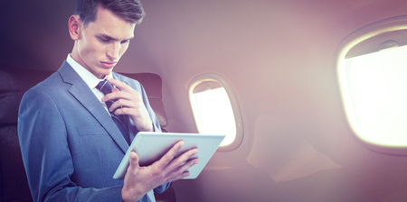 Thoughtful businessman looking at tablet pc against empty comfortable seats in plane