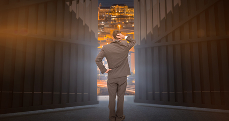 Young businessman standing back to camera scratching his head against illuminated buildings in city  3d