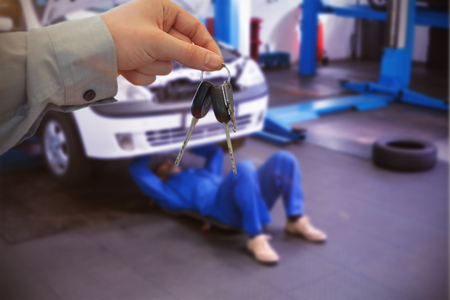 Car dealer giving keys to a customer against mechanic lying and working under car