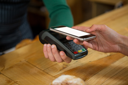Close-up of barista accepting payment through smart phone in coffee shop