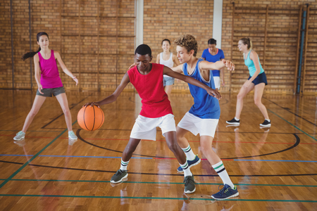 Determined high school kids playing basketball in the court