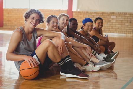 Portrait of high school kids sitting on the floor in basketball court indoors