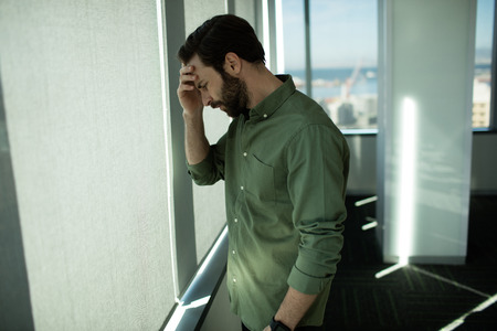 Close up of worried business executive standing by window in office on sunny day