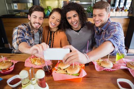 Photo pour Group of cheerful friends taking selfie in restaurant - image libre de droit