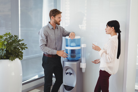 Colleagues interacting while drinking water in office